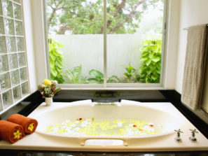 Window over bathtub filled with water and flower petals